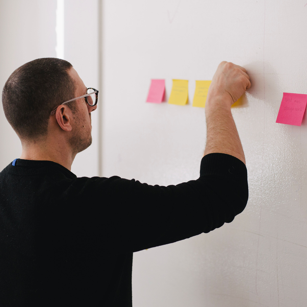 Man putting post it notes on a whiteboard